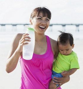 Asian mother with baby boy on beach drinking water
